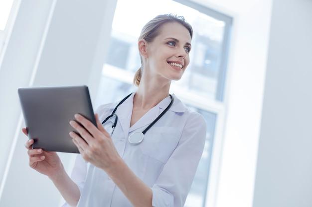 Radosny, profesjonalny lekarz lubiący godziny pracy w szpitalu, wyrażający pozytywne nastawienie i używający tabletu
