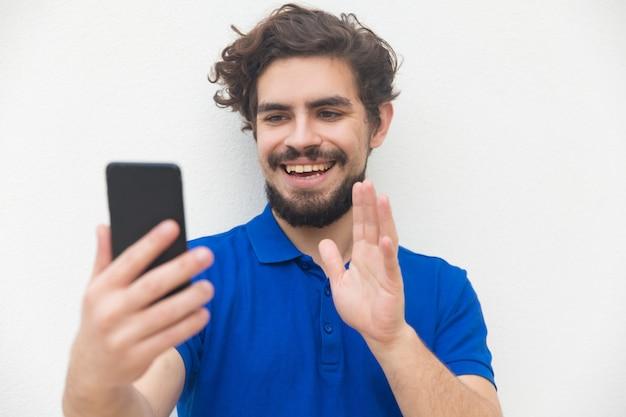 Radosny przyjacielski facet machający smartfonem cześć