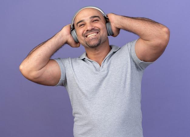 Radosny, przypadkowy mężczyzna w średnim wieku, noszący słuchawki, trzymający je za ręce, patrząc w górę na fioletowej ścianie