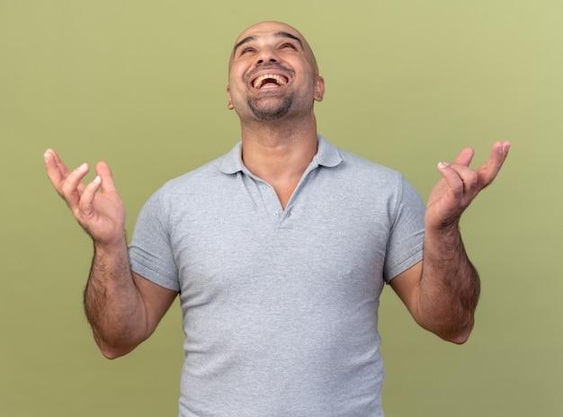 Radosny przypadkowy mężczyzna w średnim wieku pokazujący puste ręce patrzące w górę izolowane na oliwkowozielonej ścianie