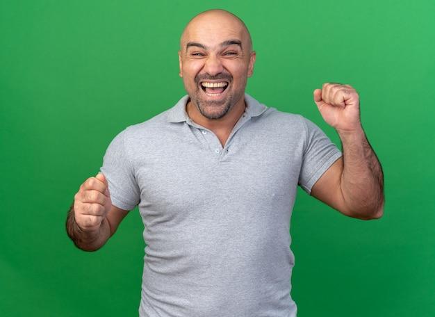 Radosny przypadkowy mężczyzna w średnim wieku robi gest tak na zielonej ścianie