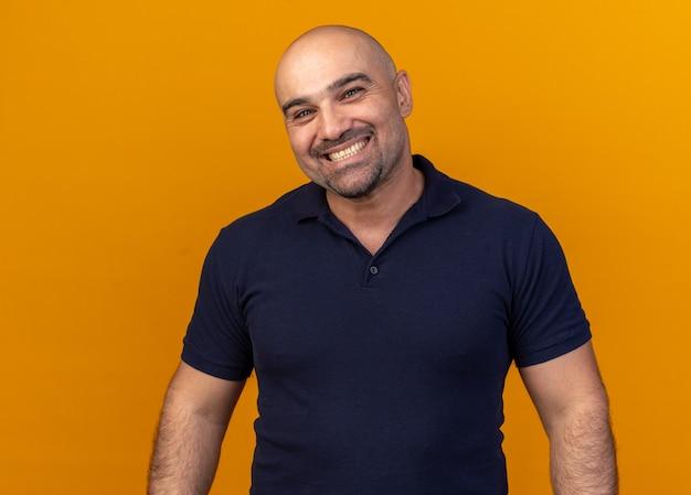 Radosny przypadkowy mężczyzna w średnim wieku uśmiechający się na pomarańczowej ścianie