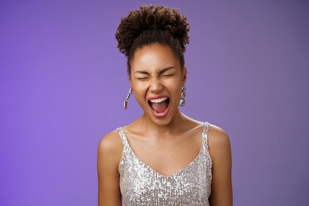 Radosny przystojny afro-amerykański stylowy młoda kobieta w srebrnej sukni wieczorowej zamknij oczy ziewanie senny zmęczony impreza całą noc stoi rozbawiony niebieskim tle chce spać. skopiuj miejsce
