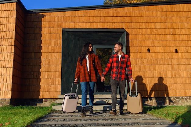 Radosny przystojny brodaty młody mężczyzna i całkiem stylowa kobieta wychodzą z nowoczesnego domu z walizkami podczas wspólnego wyjazdu na wakacje.
