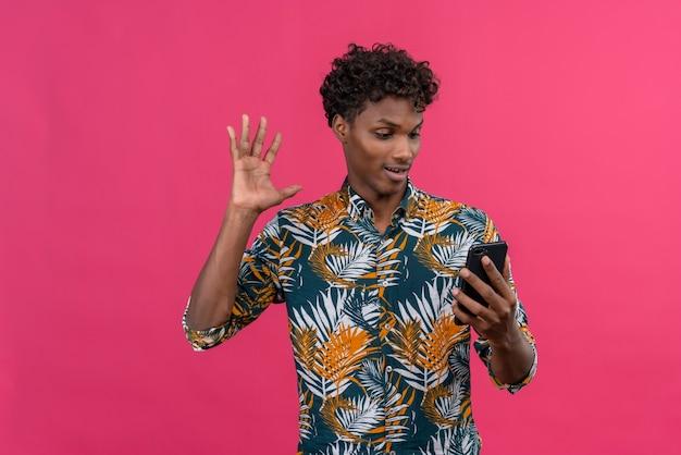 Radosny przystojny ciemnoskóry mężczyzna z kręconymi włosami w koszulce z nadrukiem w liście rozmawia z przyjacielem podczas rozmowy wideo i macha ręką na przednim aparacie telefonu komórkowego na różowym tle