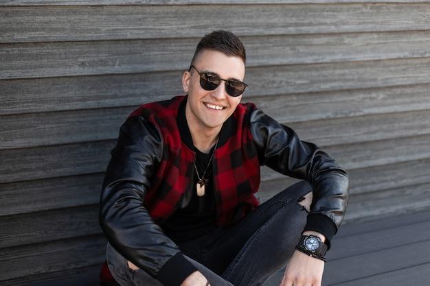Radosny przystojny hipster młody mężczyzna w modnych podartych szarych dżinsach w modnej czerwono-czarnej kraciastej kurtce w stylowych okularach przeciwsłonecznych siedzi w pobliżu drewnianej ściany w stylu vintage i cieszy się weekendem