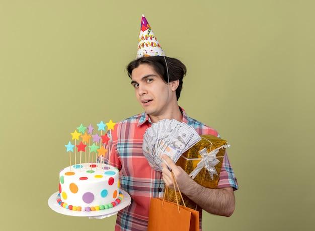 Radosny przystojny kaukaski mężczyzna w czapce urodzinowej trzyma pudełko na prezenty papierową torbę na zakupy pieniądze i tort urodzinowy
