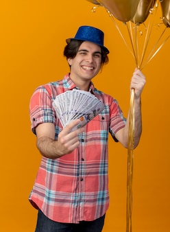 Radosny przystojny kaukaski mężczyzna w niebieskiej imprezowej czapce trzyma balony z helem i pieniądze