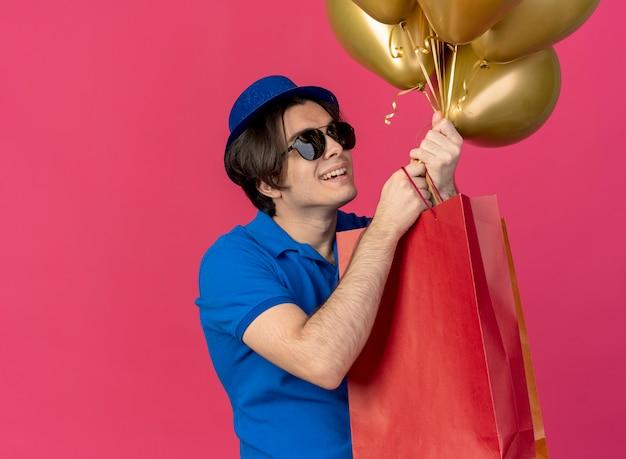 Radosny przystojny kaukaski mężczyzna w okularach przeciwsłonecznych w niebieskiej imprezowej czapce trzyma i patrzy na balony z helem i papierowe torby na zakupy