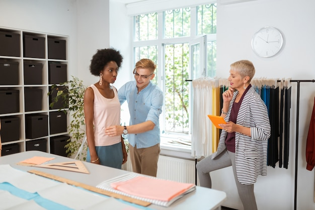 Radosny przystojny krawiec mierzący poważną młodą kobietę patrzącą na uśmiechniętą projektantkę mody