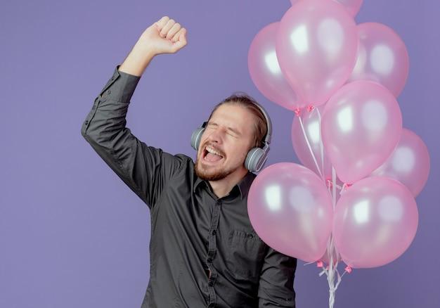 Radosny przystojny mężczyzna na słuchawkach trzyma balony z helem i podnosi pięść na białym tle na fioletowej ścianie