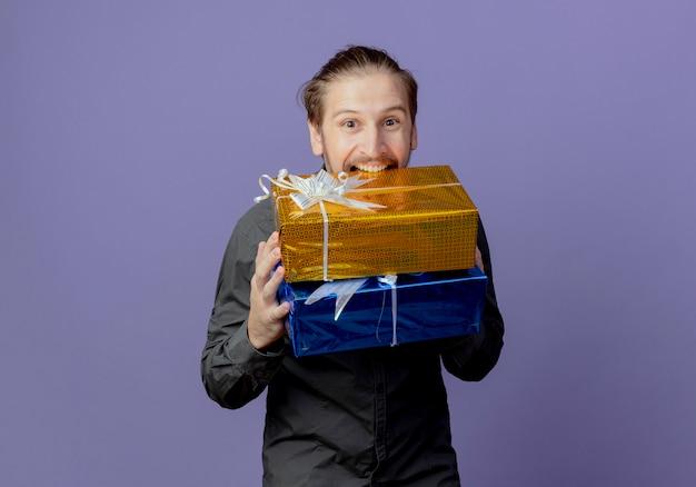 Radosny przystojny mężczyzna trzyma i gryzie pudełka z prezentami, patrząc na białym tle na fioletowej ścianie