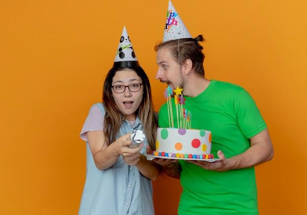 Radosny przystojny mężczyzna w kapeluszu imprezowym trzyma tort urodzinowy i patrzy na zaskoczoną młodą dziewczynę w kapeluszu imprezowym trzyma armatę konfetti odizolowaną na pomarańczowej ścianie