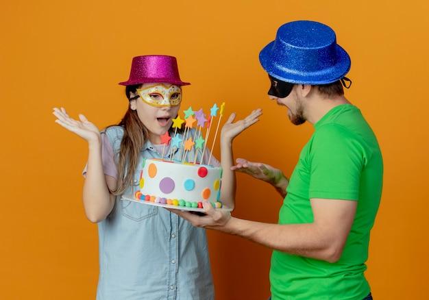 Radosny przystojny mężczyzna w niebieskim kapeluszu noszący maskę na oczy trzymający tort urodzinowy patrzący na zaskoczoną młodą dziewczynę w różowym kapeluszu i maskaradową maskę na oczy podnoszący ręce patrzący na tort