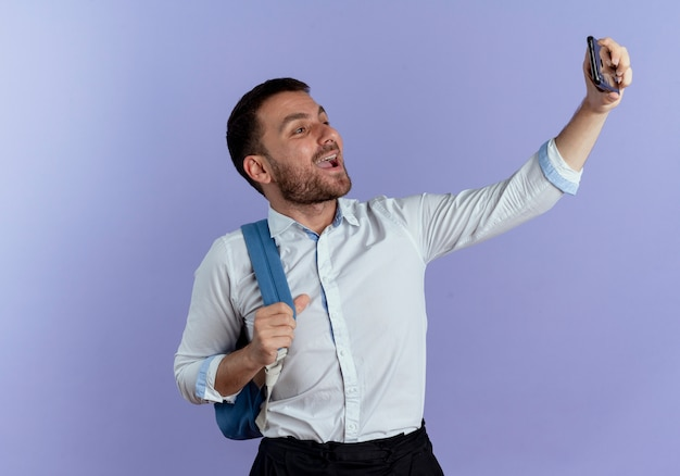 Radosny przystojny mężczyzna w plecaku trzyma telefon przy selfie na fioletowej ścianie