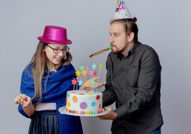 Radosny przystojny mężczyzna w urodzinowej czapce trzymający tort i dmuchający w gwizdek patrzący na zdziwioną młodą dziewczynę w okularach w różowym kapeluszu, trzyma gwizdek i patrzy na tort