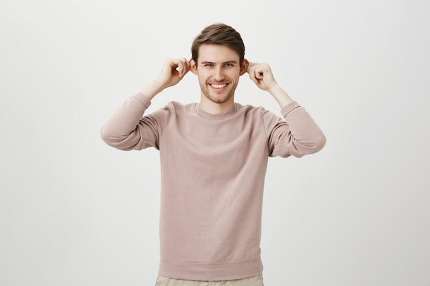 Radosny przystojny mężczyzna wyciąga uszy i uśmiecha się