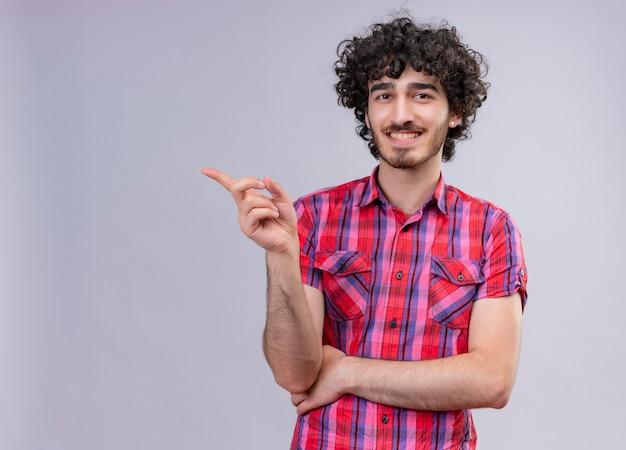 Radosny przystojny mężczyzna z kręconymi włosami w kraciastej koszuli wskazujący palcem wskazującym