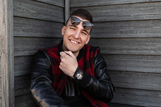 Radosny przystojny młody hipster z pozytywnym uśmiechem w modnej czerwono-czarnej kraciastej kurtce w stylowych okularach przeciwsłonecznych siedzi przy starej drewnianej ścianie i cieszy się weekendem