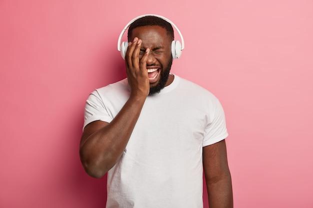 Radosny, pulchny ciemnoskóry mężczyzna śmieje się z pozytywnych emocji, zakrywa twarz ręką, relaksuje się przy muzyce, nosi nowoczesne słuchawki stereo