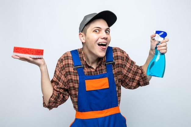 Radosny rozkładający rękę młody sprzątacz ubrany w mundur i czapkę trzymającą gąbkę ze środkiem czyszczącym