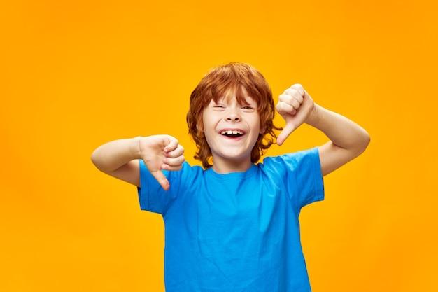 Radosny rudy chłopiec pokazujący kciuki w dół