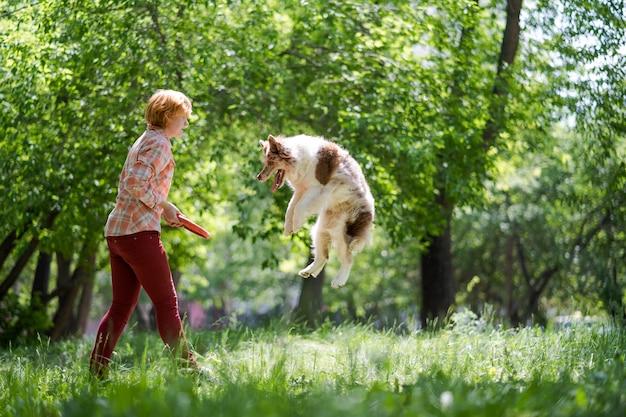 Radosny skaczący piesek i jego właściciel. kobieta rzuca psu zabawkę. zabawne spacery ze zwierzętami.