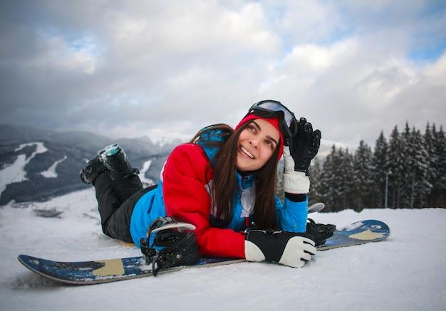 Radosny snowboarder kobieta w zimie przy ośrodkiem narciarskim