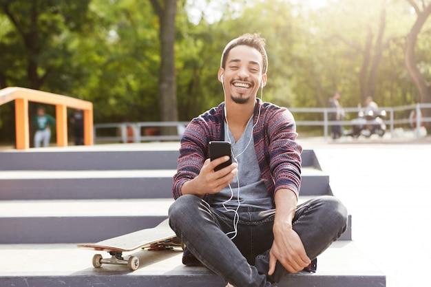 Radosny, spokojny nastolatek rasy mieszanej siedzi na ziemi na zewnątrz, słucha melodii przez telefon komórkowy