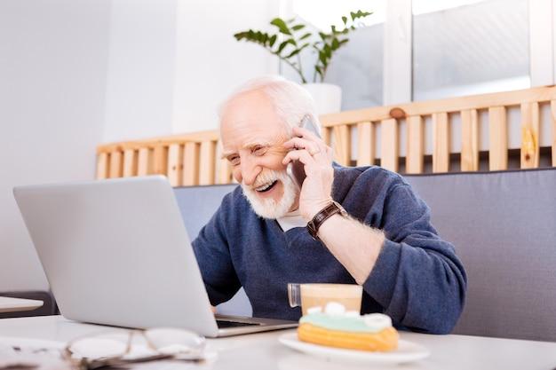 Radosny starszy wolny strzelec korzystający z laptopa i komunikujący się przez telefon