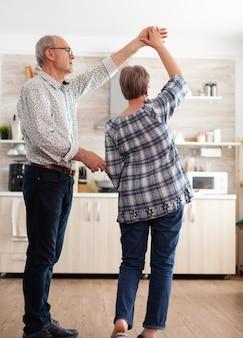 Radosny staruszek i kobieta tańczą w kuchni wcześnie rano, relaksując się po zdrowym śniadaniu. szczęśliwa para seniorów bawi się, emeryci w przytulnym domu cieszą się życiem