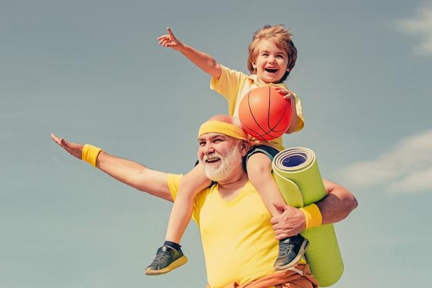 Radosny staruszek i ładny mały chłopiec uprawiający sport i zdrowy styl życia nad niebem