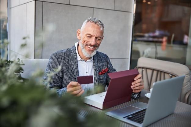 Radosny starzejący się mężczyzna patrzący na ciemnoczerwoną kartkę w ręku i uśmiechający się siedząc w kawiarni