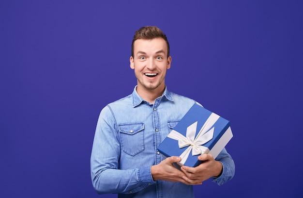 Radosny szczęśliwy facet z prezentem, patrząc prosto i uśmiechnięty.