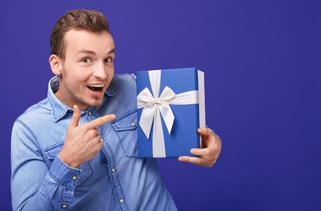 Radosny szczęśliwy młody człowiek w niebieskiej dżinsowej koszuli pokazuje palec wskazujący na prezent