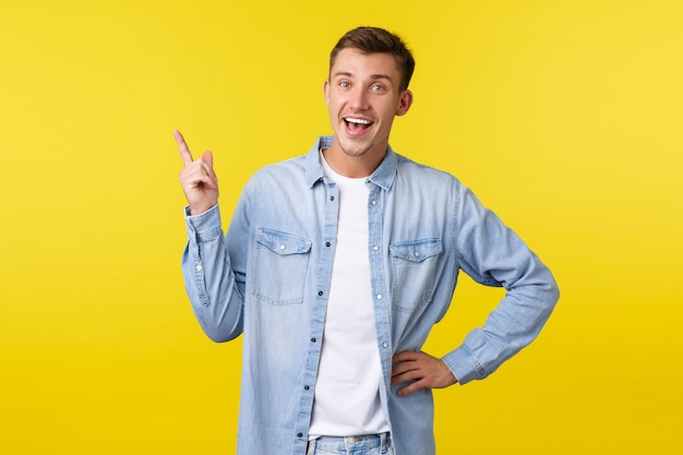 Radosny szczęśliwy uśmiechający się kaukaski mężczyzna wskazując palcem w lewym górnym rogu i patrząc aparat zachwycony. facet poleca reklamę produktu, opowiada o świetnej nowej ofercie, żółte tło.