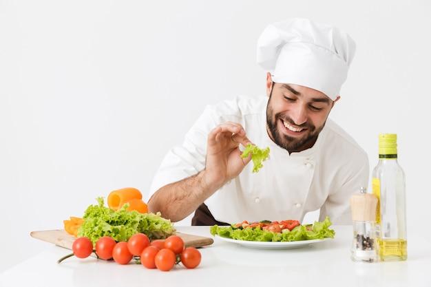 Radosny szef kuchni w kapeluszu kucharza uśmiechający się i pozujący z sałatką jarzynową w pracy odizolowanej na białej ścianie