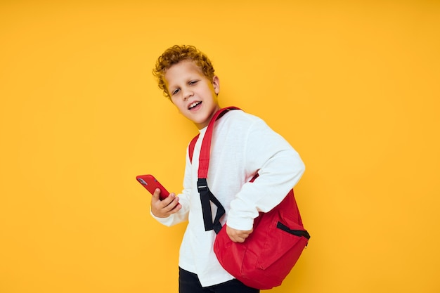 Radosny uczeń w białej bluzie telefon komórkowy czerwony plecak żółtym tle