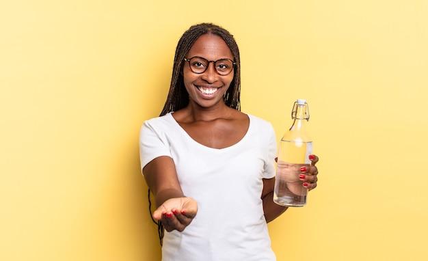 Radosny uśmiech z przyjaznym, pewnym siebie, pozytywnym spojrzeniem, oferujący i pokazujący przedmiot lub koncepcję. koncepcja butelki z wodą