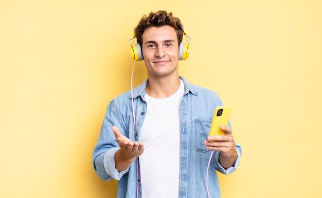 Radosny uśmiech z przyjaznym, pewnym siebie, pozytywnym spojrzeniem, oferujący i pokazujący przedmiot lub koncepcję. koncepcja słuchawek i smartfona