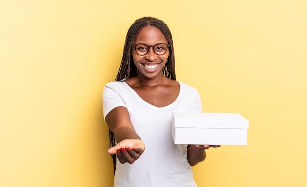 Radosny uśmiech z przyjaznym, pewnym siebie, pozytywnym spojrzeniem, oferujący i pokazujący przedmiot lub koncepcję oraz trzymający puste pudełko
