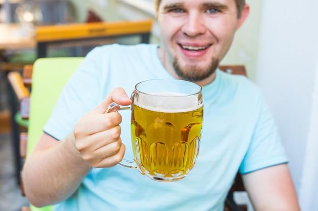 Radosny uśmiechnięty mężczyzna trzymający duży kufel piwa na zewnątrz