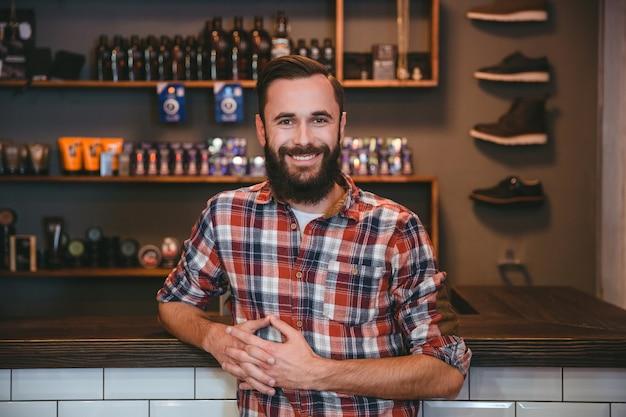 Radosny uśmiechnięty zadowolony brodaty mężczyzna w kraciastej koszuli pozuje w salonie fryzjerskim