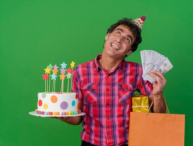 Radosny w średnim wieku kaukaski mężczyzna ubrany w czapkę urodzinową, trzymając tort urodzinowy worek papierowy prezent i pieniądze patrząc w górę na białym tle na zielonym tle