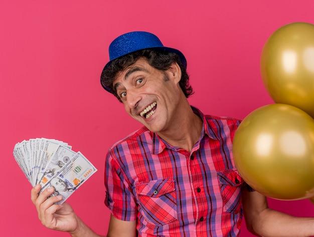 Radosny w średnim wieku kaukaski mężczyzna ubrany w kapelusz partii trzymając balony i pieniądze patrząc na kamery na białym tle na szkarłatnym tle