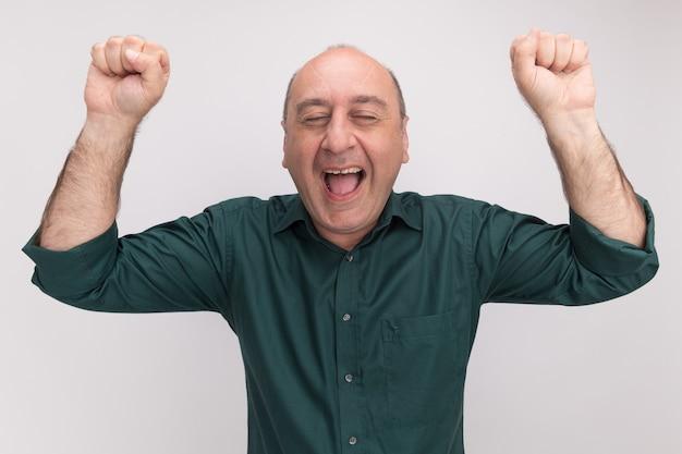 Radosny z zamkniętymi oczami mężczyzna w średnim wieku ubrany w zieloną koszulkę podnosząc pięści na białym tle na białej ścianie