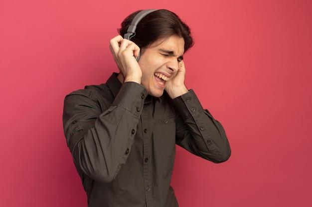 Radosny z zamkniętymi oczami młody przystojny facet ubrany w czarną koszulkę ze słuchawkami słuchać muzyki na białym tle na różowej ścianie