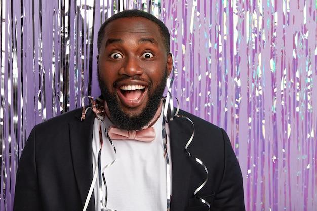 Radosny zaskoczony afro amerykanin z zębatym uśmiechem, białymi zębami