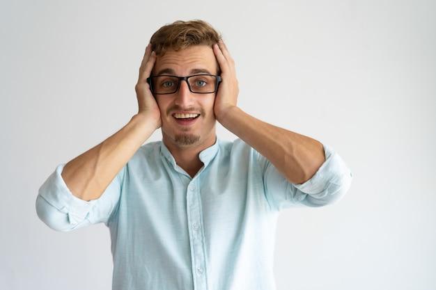 Radosny zaskoczony facet w okularach uczących się wspaniałych wiadomości.