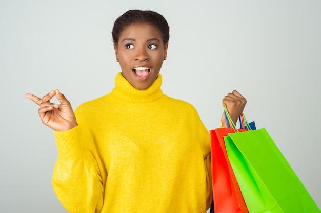 Radosny zdumiony klient trzyma kolorowe torby na zakupy